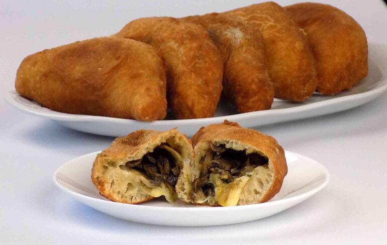 Zdjęcie przedstawiające bułeczki drożdżowe faszerowane pieczarkami i serem według przepisu https://kuchnianawypasie.pl/