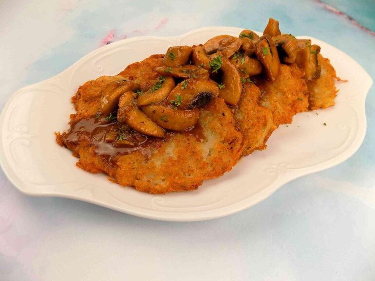 zdjęcie przedstawiające placki ziemniaczane w sosie pieczarkowym według przepisu z bloga kulinarnego kuchnia na wypasie